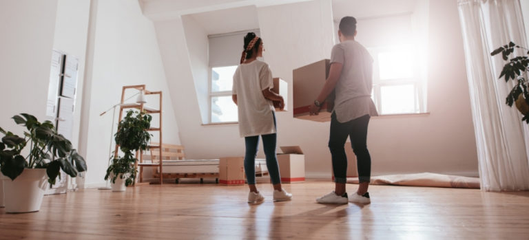 Two people holding boxes in an empty house