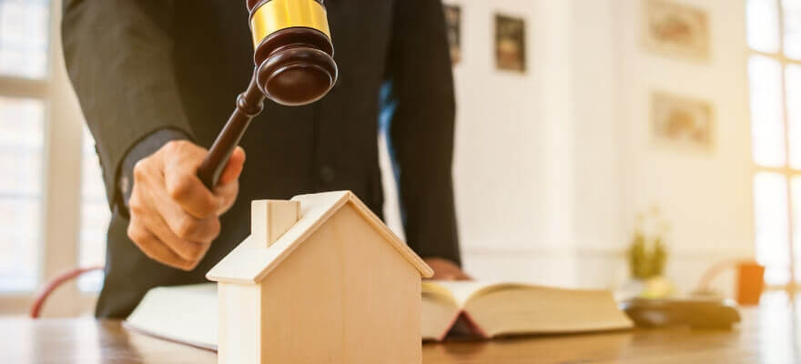 Auctioneer, gavel and little wooden house