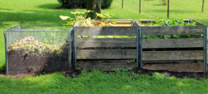 3 timber pallet compost boxes in a green field
