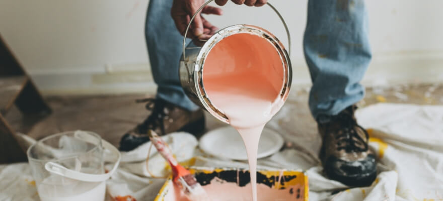 Peach coloured paint pouring into a tray