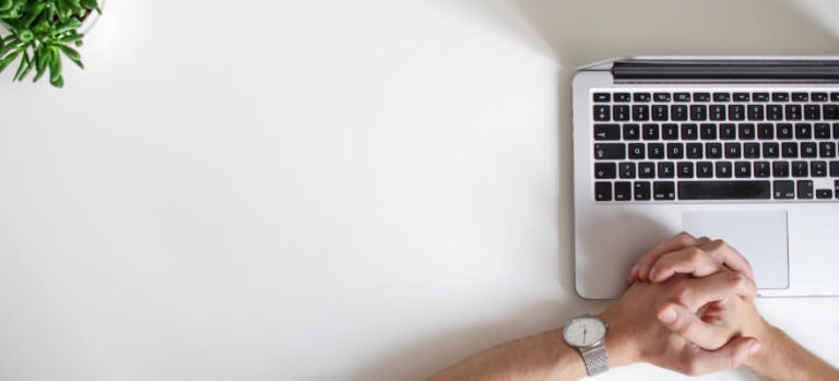White desk and laptop with mans hands