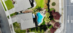 Birds eye view of two houses and a pool