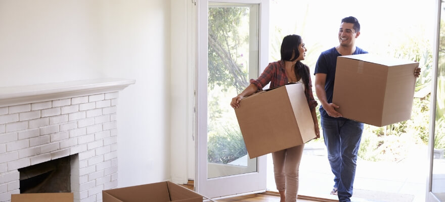 Woman and man walking into empty house carrying boxes