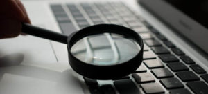 Magnifying glass on keyboard laptop