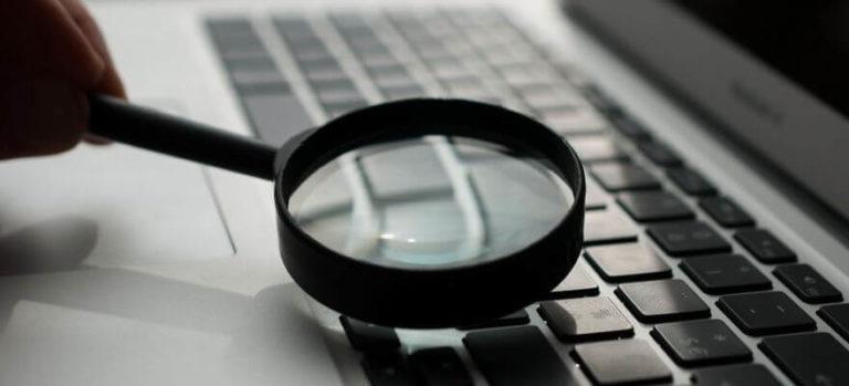 Magnifying glass on keyboard laptop