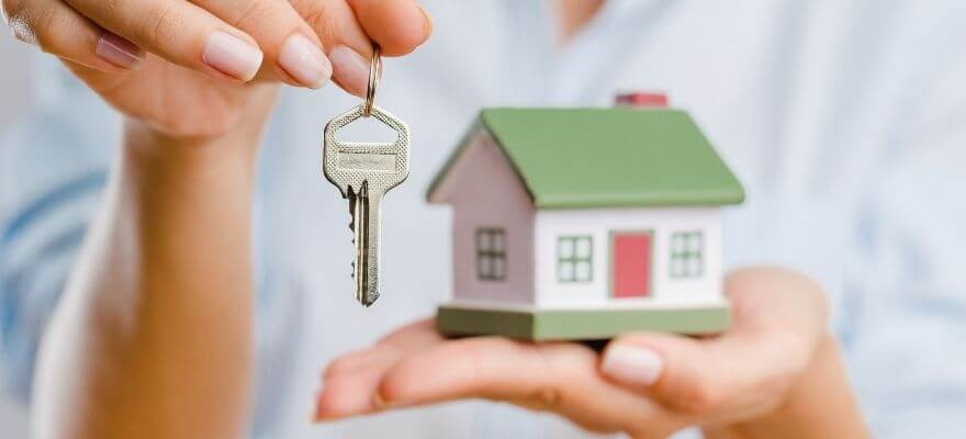 Hand holding a small house and a key
